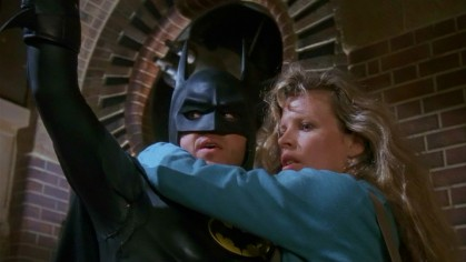"Batman (Michael Keaton) offers reporter Vicki Vale (Kim Basinger) a rescue in Tim Burton's ""Batman"" (1989)."