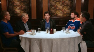 "Adam West talks with Kevin Smith (in a Fatman hockey jersey) and other accomplished admirers in ""Bats of the Round Table."""
