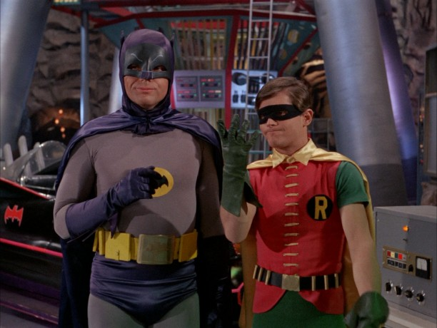 In the Batcave, in front of the Batmobile, Batman (Adam West) and Robin (Burt Ward) consider and count five Batclues.