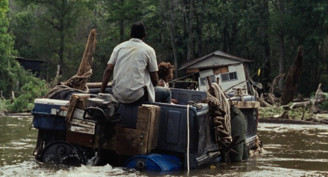 In a pick-up truck bed, father and daughter navigate the waters of their storm-ravaged community known as The Bathtub.
