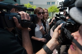 Nicki (Emma Watson) attracts paparazzi attention outside the courtroom.