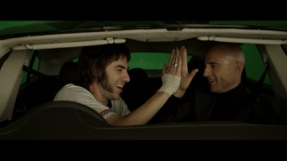 High-five! Sacha Baron Cohen and Mark Strong share a moment in a green screen driving scene from the gag reel.