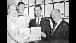 A bunch of suited men (including Friz Freleng) proudly hold up documents in one of the image gallery's unclear behind-the-scenes photos.