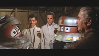 Robots Bob and V.I.N.CENT share the screen with Robert Forster, Joseph Bottoms, and a mustachioed Ernest Borgnine.