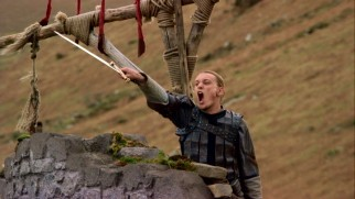 Arthur (Jamie Campbell Bower) shows his brave side by shouting, wielding a sword, and tying his hair into a tiny braid.