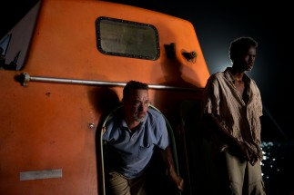 The drama continues for multiple days and nights, with Captain Phillips (Tom Hanks) being taken hostage inside the Alabama's covered orange lifeboat.
