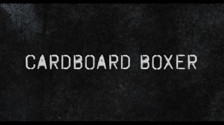 The theatrical trailer gives us a functional title font for Cardboard Boxer.