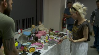 "¥o-Landi Vi$$er surveys a table of props with which she can decorate her character's slum home in ""Keep It Gangster."""