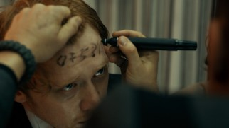 Rupert Grint has a phone number written on his forehead in marker in the thankless comic relief supporting role of Karl.
