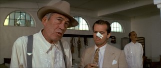 AFI-ranked villain Noah Cross (John Huston) talks to Jake (Jack Nicholson), whose nosy nose has been cut and thickly bandaged.
