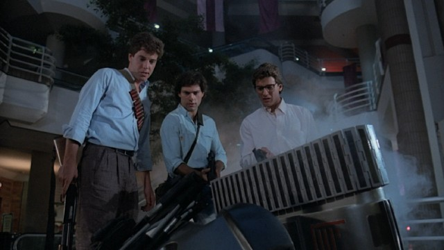 "One down, two to go: the preppy men of ""Chopping Mall"" (Nick Segal, Russell Todd, and Tony O'Dell) take out a killer robot."