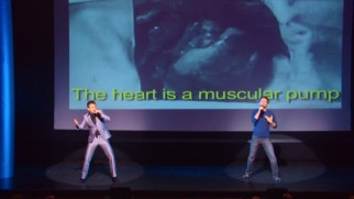 "Hard (Chris Hardwick) 'n Phirm (Mike Phirman) perform ""Corazón"", which the English translations behind them reveal as a factual song all about the human heart."