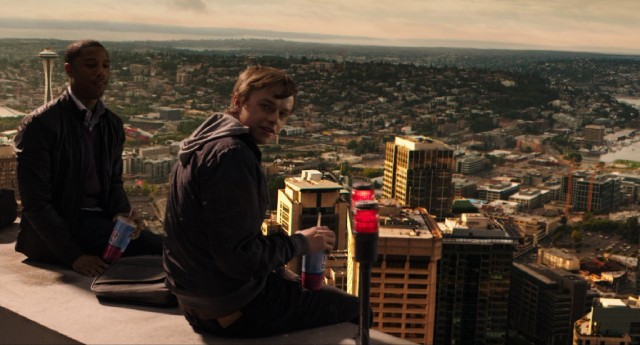 High above Seattle, Steve (Michael B. Jordan) and Andrew (Dane DeHaan) drink soda and use telekinesis to make their camera float.
