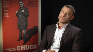 "In ""All About 'Chuck'"", a cleaner-shaven Liev Schreiber speaks next to the poster of the film he wrote, produced and stars in."