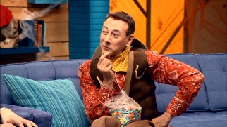 A cowboy-costumed Pee-Wee Herman savors a single piece of his all-chocolate trail mix in the Halloween episode.