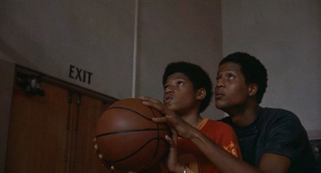 "Nathaniel ""Cornbread"" Hamilton (Jamaal Wilkes) helps his supposed cousin/certain admirer Wilford Robinson (Laurence Fishburne) with his jump shot in ""Cornbread, Earl and Me."""