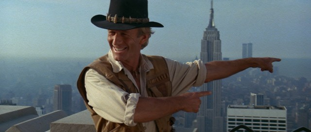 "In ""'Crocodile' Dundee"", Australian outdoorsman Michael Dundee (Paul Hogan) journeys to New York City for the first time and poses for pictures on the Empire State Building's Observation Deck."