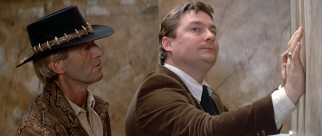 Crocodile Dundee (Paul Hogan) makes a DEA agent (Stephen Root in his film debut) uncomfortable at a urinal.