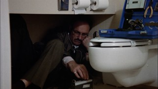 From a bathroom floor, skilled bugger Harry Caul (Gene Hackman) eavesdrops on the hotel room next door.