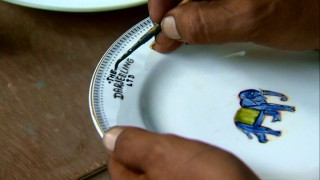 A local man paints the name of the train on an elephant-adorned plate, one of countless pieces of handmade production design created for the film.