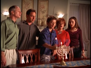 Louis lights the first candle of the menorah because that's what Jewish people do, you see.