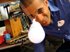 "Asa Kalama squints a one-eyed look at the Newton's cradle he teaches how to build on ""Energy."""