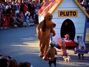 "Dressed and walking upright, real life canines flock to costumed performer Pluto in the Christmastime Fantasy on Parade seen in ""Disneyland Around the Seasons."""