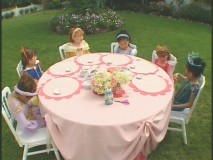 Girls dressed as Disney princesses gather round the table for Princess Craft Time!