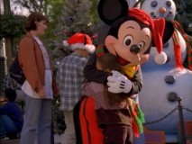"""Holidays at the Disneyland Resort"" shows what you can expect to get out of a Christmastime visit to Anaheim. A hug from Mickey in a Santa hat and a snowman gleefully watching."