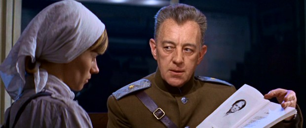 General Yevgraf Zhivago (Alec Guinness) shows labor camp worker Tonya (Rita Tushingham) a picture of his half-brother, who he suspects is her father. Yevgraf is star of the film's framework and occasional narrator.