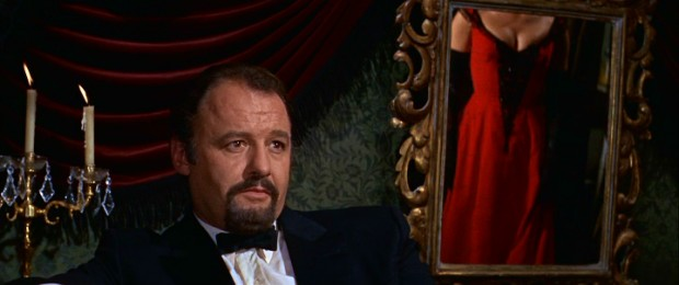 The complicated and none too charming Viktor Komarovsky (Rod Steiger) checks out the goods as his mistress's daughter Lara turns and models a red dress (seen in mirror).
