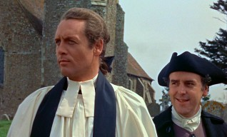 By day, Dr. Christopher Syn (Patrick McGoohan) is Dymchurch's mild-mannered vicar. Smiley sexton and confidant Mr. Mipps (George Cole) stands behind him.