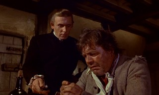 Prosecutor Frank Fragg (Alan Dobie) gives sweaty farmer Joseph Ransley (Patrick Wymark) the first of 1,000 reasons to betray his financial redeemer, the Scarecrow.