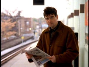 With advance newspaper in hands, Gary looks to Chicago's L train tracks in anticipation of calamity.
