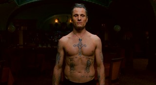 "Nikolai shows off his tattooed body, the calling card of a Russian criminal, to a group looking to give him some new body art. If you think this is revealing, it's nothing compared to what the studio calls Viggo Mortensen's ""now infamous steam room fight scene""!"