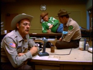 Hoover's disapproving father Sheriff Niebold (Warren Kemmerling) is upset by another disconcerting deputy report, while the car's owner/racer Big Bubba Jones (Dave Madden) and Clark (Rance Howard, father of Ron) pay little attention.