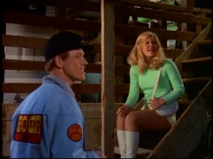 In one of their few scenes outside a moving vehicle, Hoover (Ron Howard) and the leggy, hot-panted Darlene (Christopher Norris) smile at the site of a horse and surrey in this stable.