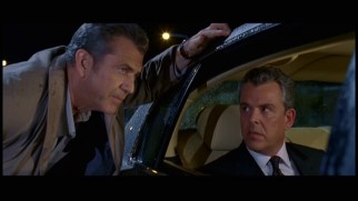 Craven (Mel Gibson) remains outside the car in confronting Jack Bennett (Danny Huston) in this alternate scene.