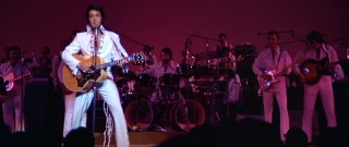 The King of Rock 'N Roll takes hold of Las Vegas with a guitar and white jumpsuit.