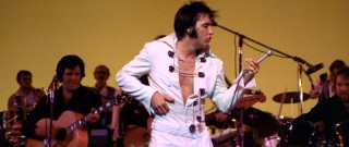 Elvis plays a little air guitar.
