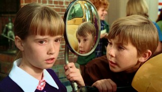 Tia Malone (Kim Richards) explains an urgent premonition she has to her brother Tony (Ike Eisenmann), who's reflected in a school bus sideview mirror.