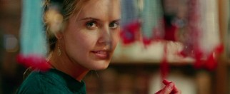 Bay (Maggie Grace) smiles at an Indian marketplace during one of Travis' colorful dreams.