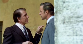 "Mafia Don Corrasco (Richard Conte) conspires with corrupt police commissioner Torri (Gianni Garko) in ""The Boss."""