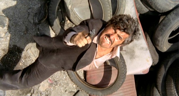 "Luca Canali (Mario Adorf) shoots up at a heap in the memorable junkyard shootout that concludes ""The Italian Connection."""