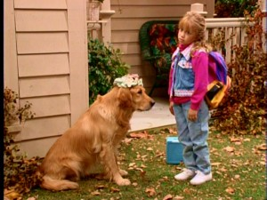 While she's no longer the only cute, young one, Michelle still receives a considerable amount of attention in the part now needlessly shared by Mary-Kate and Ashley Olsen. Here, she passes on her headwear to Comet the dog.