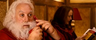 In bed with his wife Annette (Miranda Richardson), fat-fingered Santa Claus (Paul Giamatti) gets a jail call from his brother.