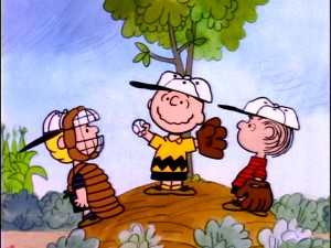 Even with a tree on the pitcher's mound and flowers all around, the game must go on, something Charlie Brown seems uncharacteristically happy about.