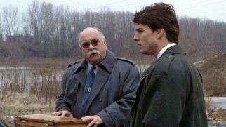 Security chief Wilford Brimley surprises Mitch not with diabetes testing supplies from Liberty but incriminating photos from the Cayman Islands.