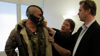 Bane (Tom Hardy) has his costume inspected by costume designer Lindy Hemming and director Christopher Nolan.