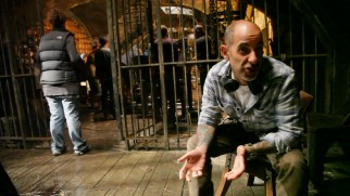 "Creator David S. Goyer addresses the camera from a prison set in ""Constructing Da Vinci."""